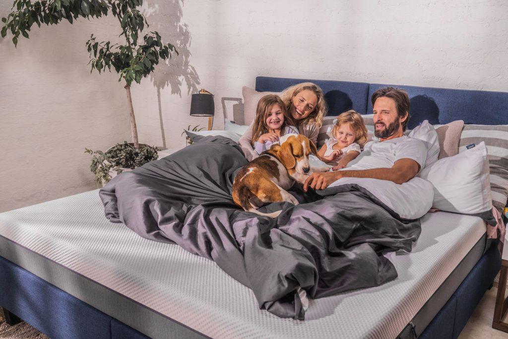 familia en cama con perro